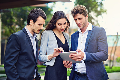 Buy stock photo Shot of businesspeople using a tablet outside