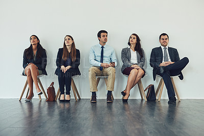 Buy stock photo Studio shot of a group of businesspeople looking bored while waiting in line