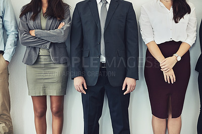 Buy stock photo Cropped studio shot of a group of young businesspeople standing together in a row