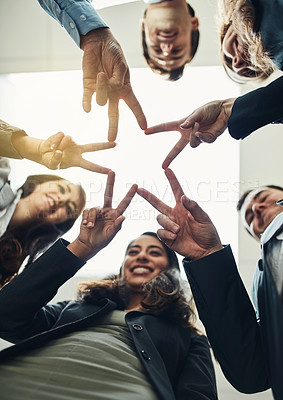 Buy stock photo Low angle shot of a group of young businesspeople joining their hands in a modern office