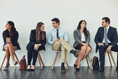 Buy stock photo Studio shot of a group of businesspeople talking while waiting in line