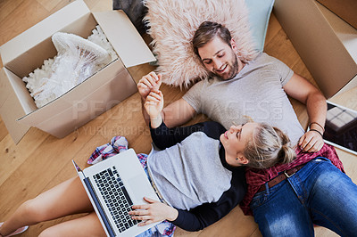 Buy stock photo High angle shot of a happy young couple using a laptop in their new home