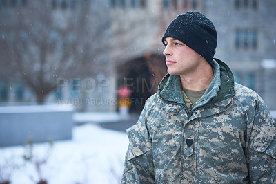 Buy stock photo Shot of a young soldier standing outside on a snowy day at military school