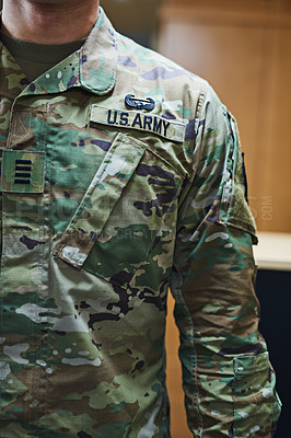 Buy stock photo Cropped shot of a soldier wearing camouflage fatigues with a badge attached to velcro on his chest