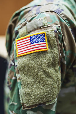 Buy stock photo Cropped shot of a soldier wearing camouflage fatigues with an american flag for a patch