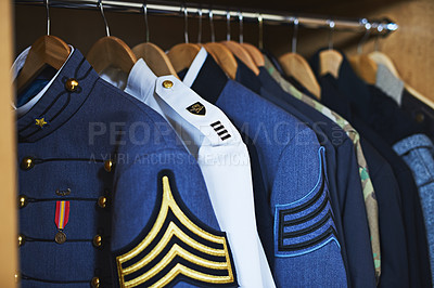 Buy stock photo Shot of various military jackets hanging in a closet