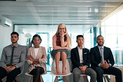 Buy stock photo Portrait of a group of young businesspeople sitting in a row in their office