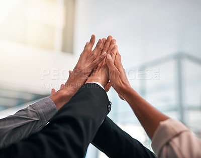 Buy stock photo Cropped shot of a group of unrecognizable businesspeople high fiving while standing in their office