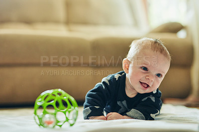 Buy stock photo Shot of an adorable baby boy playing with a toy ball at home
