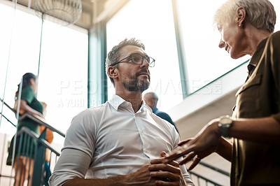 Buy stock photo Shot of two businesspeople talking to each other while standing on a stairwell