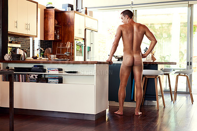 Buy stock photo Rearview shot of a handsome young shirtless man making breakfast in the kitchen at home