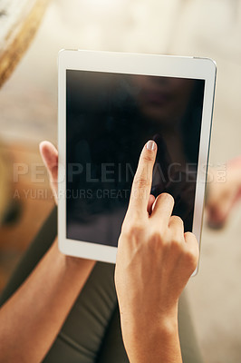 Buy stock photo Closeup of an unrecognizable woman browsing on a digital tablet while being seated at a cafe outside during the day