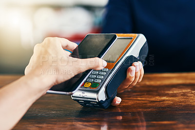 Buy stock photo Closeup of an unrecognizable person using her phone to scan and pay a bill on a card machine at a cafe during the day