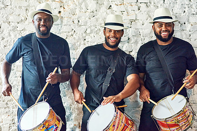 Buy stock photo Cropped portrait of a group of handsome young male drummers playing at Carnival