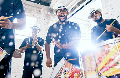Buy stock photo Low angle portrait of a group of handsome young male drummers playing at Carnival