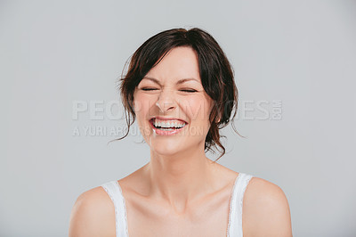 Buy stock photo Studio shot of an attractive woman laughing against a gray background
