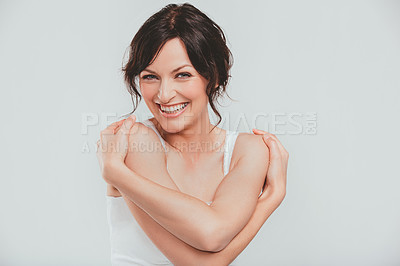 Buy stock photo Studio shot of an attractive woman hugging herself against a gray background