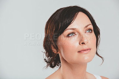 Buy stock photo Studio shot of an attractive woman looking thoughtful against a gray background