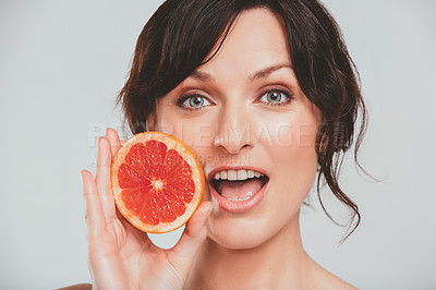 Buy stock photo Cropped shot of a beautiful woman holding a grapefruit up to her face