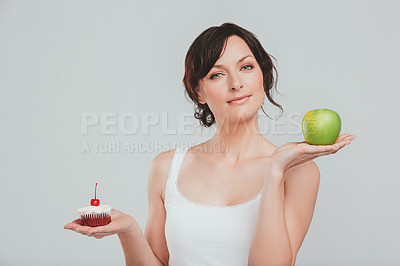 Buy stock photo Studio shot of a woman deciding between healthy and unhealthy foods