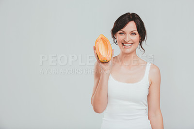 Buy stock photo Studio shot of a beautiful woman holding a sweet melon against a grey background
