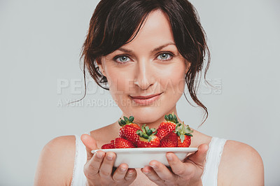 Buy stock photo Shot of a beautiful woman holding a plate of strawberries against a grey background