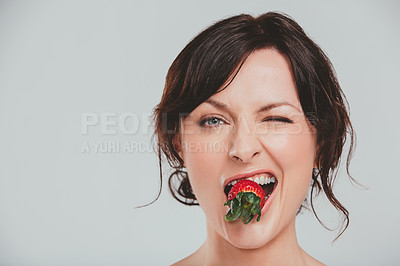 Buy stock photo Studio shot of an attractive woman eating a snack against a gray background