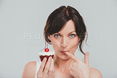 Buy stock photo Studio shot of an attractive woman holding a cupcake against a gray background