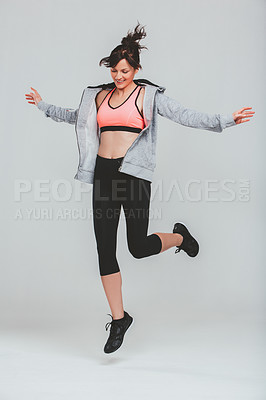 Buy stock photo Studio shot of a sporty young woman jumping against a grey background