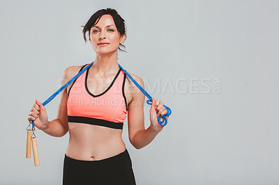 Buy stock photo Studio portrait of a sporty young woman holding a skipping rope against a grey background