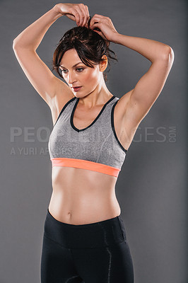 Buy stock photo Studio shot of a sporty young woman tying her hair against a grey background