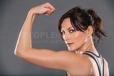 Buy stock photo Studio portrait of a sporty young woman flexing her muscles against a grey background