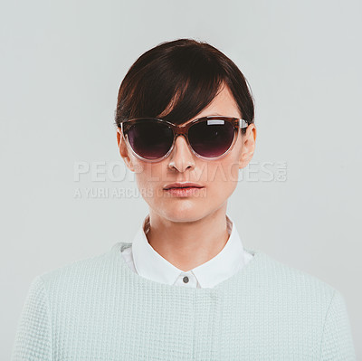 Buy stock photo Studio portrait of an attractive woman wearing sunglasses and a preppy outfit against a gray background