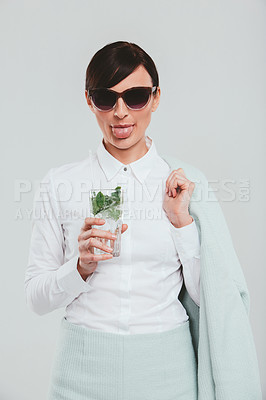 Buy stock photo Studio portrait of an attractive woman wearing a preppy outfit and sticking out her tongue against a gray background