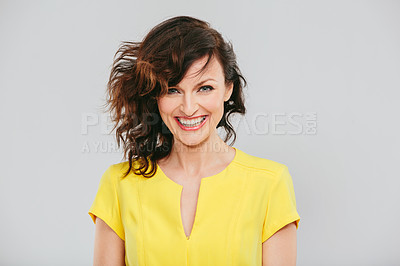 Buy stock photo Studio portrait of an attractive woman posing against a gray background