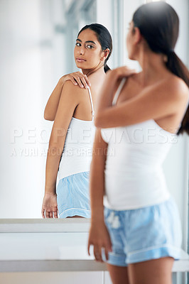 Buy stock photo Cropped shot of an attractive young woman inspecting her back in front of the bathroom mirror