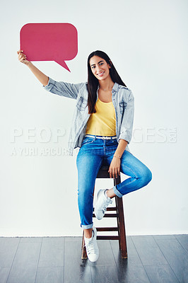 Buy stock photo Studio shot of an attractive young woman holding a speech bubble