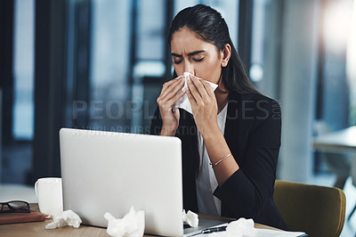 Buy stock photo Shot of a young businesswoman blowing her nose while working in an office
