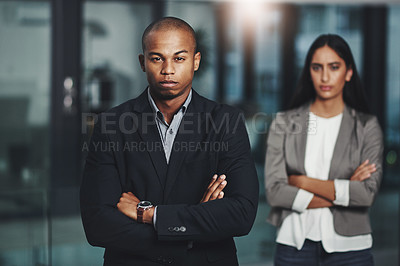 Buy stock photo Portrait of a young businessman standing in an office with his colleague in  the background