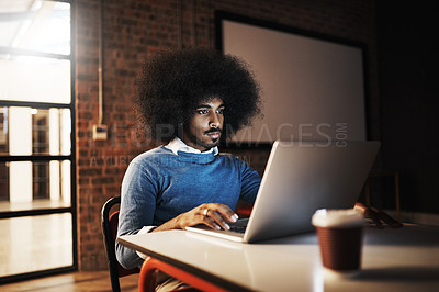 Buy stock photo Cropped shot of a handsome young male designer using his laptop while working late in the office