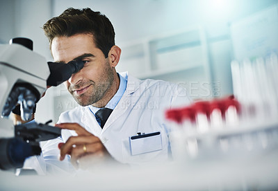 Buy stock photo Shot of a scientist using a microscope in a lab