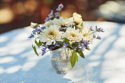 Buy stock photo Shot of a metal vase filled with flowers on table at a tea party outside