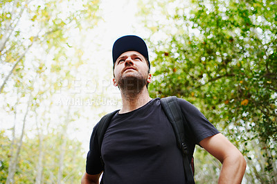 Buy stock photo Low angle shot of a young man hiking through the forest