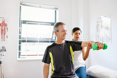 Buy stock photo Shot of a mature man exercising with dumbbells with the help of a physiotherapist