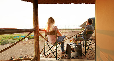 Buy stock photo Rearview shot of an unrecognizable couple looking at the view while sitting on their suites veranda at a resort in nature