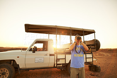 Buy stock photo Shot of a young man using binoculars while on a safari