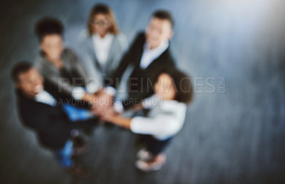 Buy stock photo Defocused shot of a group of businesspeople joining their hands together in a huddle