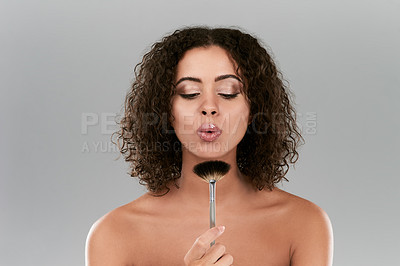 Buy stock photo Studio shot of a beautiful young woman blowing a make up brush against a gray background