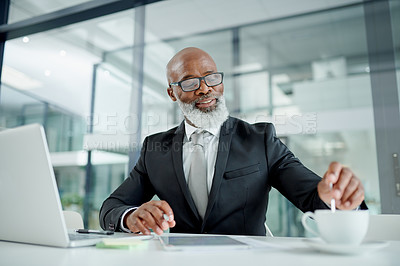 Buy stock photo Shot of a mature businessman stirring a cup of coffee in an office