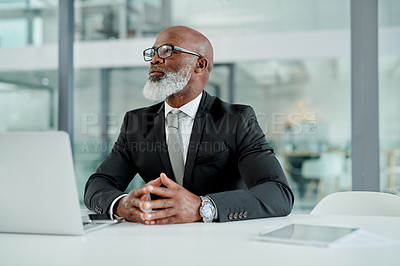 Buy stock photo Shot of a mature businessman looking thoughtful while working in an office